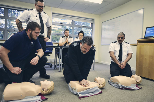 A prison officer simulates CPR on a first aid dummy while 5 others watch. There are 2 other CPR dummies on the floor.