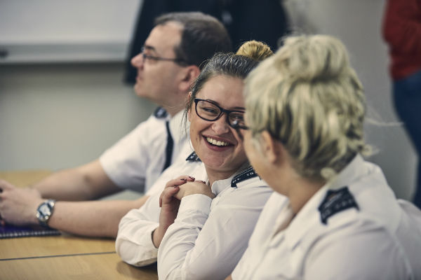 Prison officers in a classroom smiling