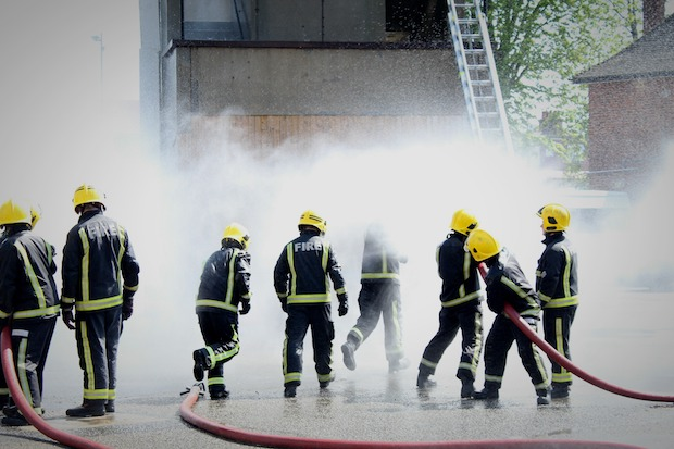 8 people dressed in fire brigade uniform hosing using a fire hose against a wall.