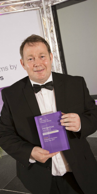Gareth is dressed in a tuxedo and holds a purple glass rectangular award for 2017 probation champion