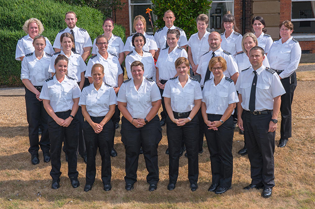 HMPPS Senior Leadership Scheme group picture - 22 men and women stand in 3 lines dressed in black and white prison officer uniforms. They stand outside with a building and hedge behind them