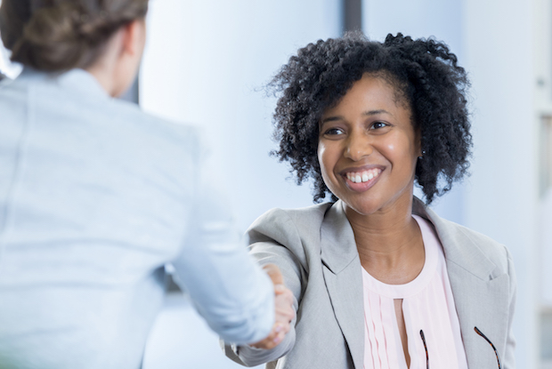 Confident CEO greets potential employee before job interview. The interviewee's back is to the camera.