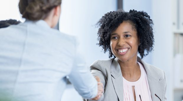 Confident interviewer greets potential employee before job interview.